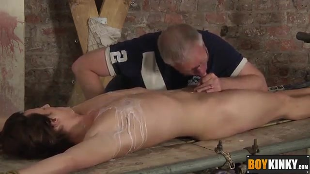 The older gay man dominates a bound young man